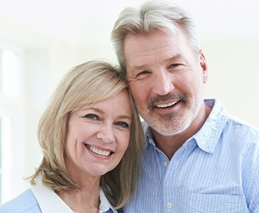 Man and woman with healthy smile after periodontal therapy