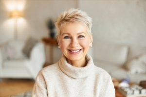 Woman smiling with healthy gums while wearing a sweater